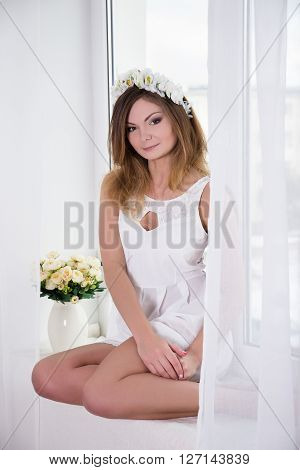 Beautiful Woman In White Dress With Flowers Crown On Head Sitting Near The Window