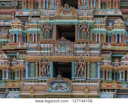 Trichy India - October 15 2013: Detail of the massive Rajagopuram of Ranganathar Temple. Focus on a couple of the openings protected by Dwarapalakas. Pastel colors entire photo of pillars and statues. Lakshmi on lotus showered by elephants.