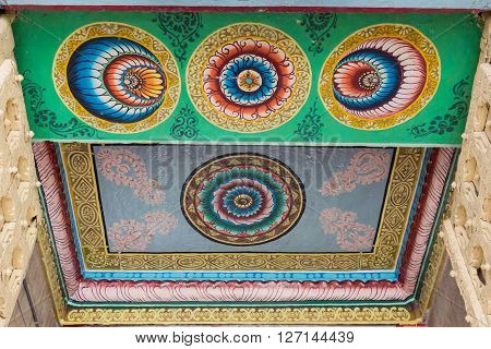 Trichy India - October 15 2013: Ceiling paintings in bright yellow red and blue colors show circles mandalas with lotus symbols. Entrance gopuram of Ranganathar Temple.