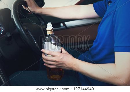 Man holding a bottle of liquor while driving in vintage tone