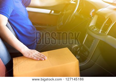 Delivery Man Driving A Truck With Cardboard Package On The Front Seat (vintage Tone)