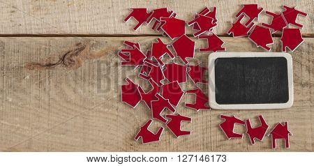 Many red house symbol on wooden background. Real-estate concept