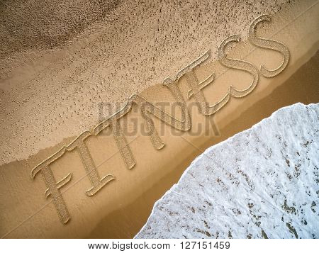 Fitness written on the beach