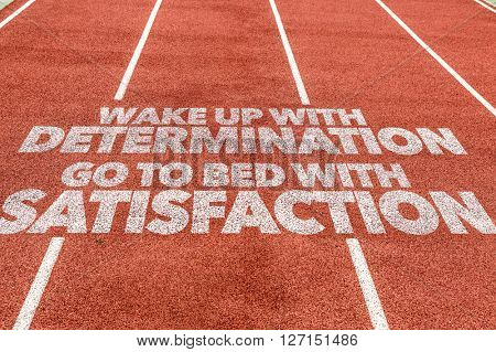 Wake Up With Determination Go To Bed With Satisfaction written on running track