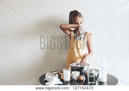 10 years old preteen girl dressed in cotton apron is cooking holiday pie on the table over wall, organic food, lifestyle photo