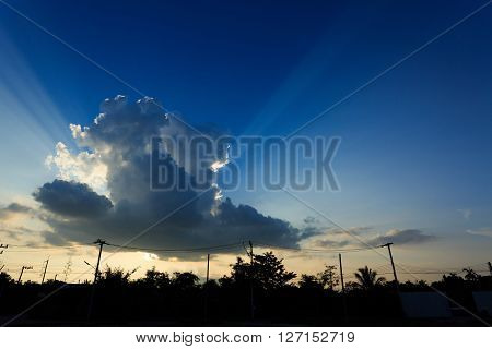 Sunlight Through Cloud On Clear Blue Sky With Silhouette Landscape