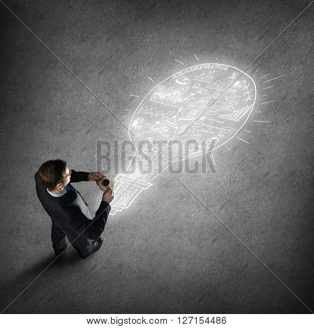 Top view of thinking businessman with coffee cup looking at plan sketches on floor