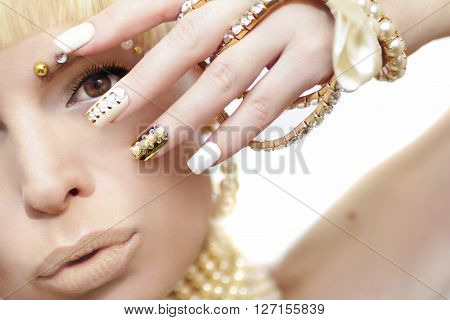 Pearl manicure with rhinestones on a gold background and pastel nails on female hand with decoration.