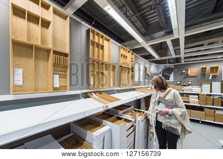 PARIS FRANCE - APR 12 2016: Elegant woman buying kitchenware and divers kitchen tool inside the IKEA furniture mall store