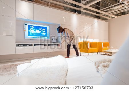 PARIS FRANCE - APR 12 2016: Woman choosing modern living room furniture and TV sets in the modern IKEA shopping furniture mall in Paris