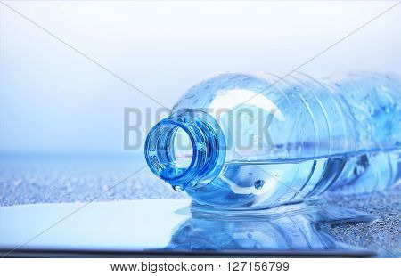 Drop Of Water Falling From Plastic Bottle With Reflection