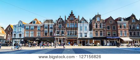 Delft, Netherlands - April 8, 2016: Colorful street panoramic view with traditional dutch houses on the square, bicycles, people walking in downtown of popular Holland destination