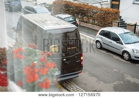 PARIS FRANCE - DEC 10 2015: POV of customer at UPS United Parcel Service van delivery brown ups van leaving after dlivering the on time delivering package parcel