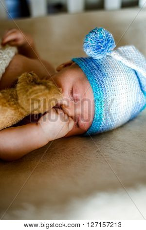 Two month old baby sound asleep in his crib with a handy toy