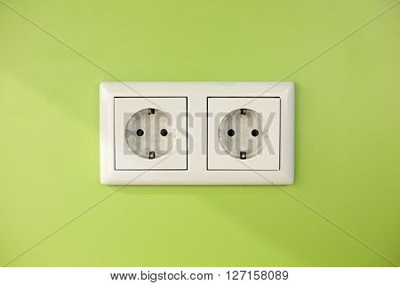 Electric outlets on green wall