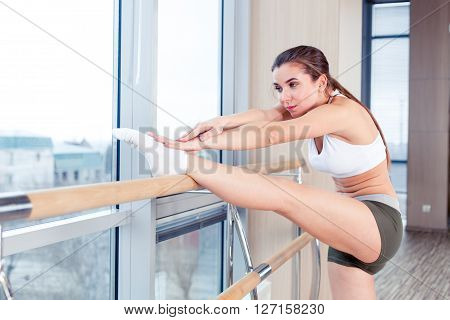 Woman standing near barre in fitness center.