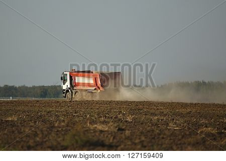 Truck at a road construction site with dust in the air