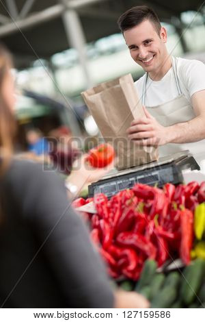 smile salesman measuring organic vegetables in grocery store