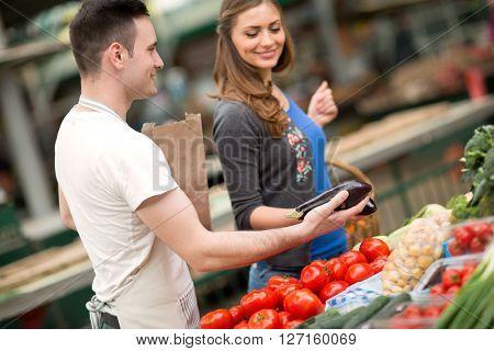salesman holding eggplant at street market