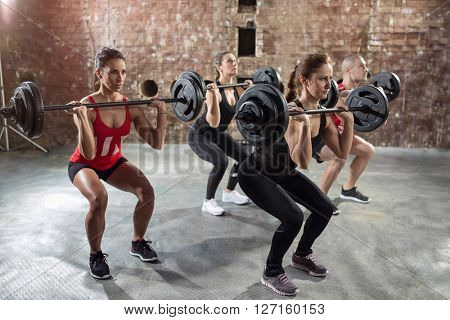 muscular bodybuilders have body pump training with dumbbell