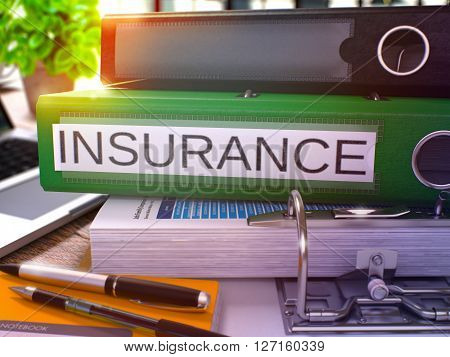 Insurance - Green Office Folder on Background of Working Table with Stationery and Laptop. Insurance Business Concept on Blurred Background. Insurance Toned Image. 3D.