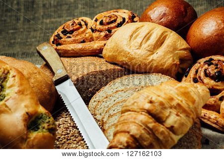 Sliced bread assortment of baked bread and knife on wooden table