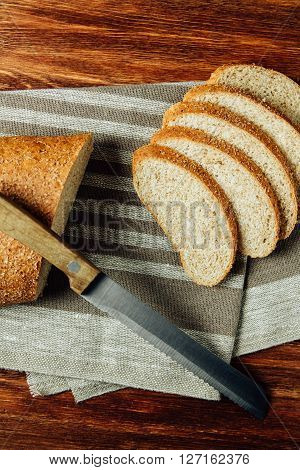 Sliced bread and knife on linen cloth on wooden table