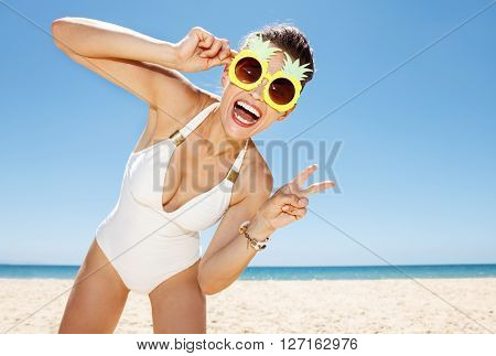 Woman In Pineapple Glasses Showing Victory Gesture At Beach