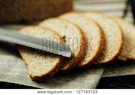 Sliced bread and knife on linen cloth.