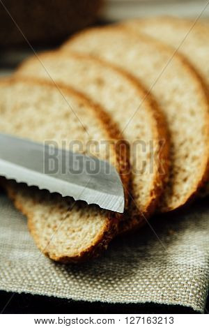 Sliced bread and knife on linen cloth. Close up photo.