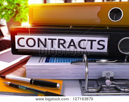 Black Ring Binder with Inscription Contracts on Background of Working Table with Office Supplies and Laptop. Contracts Business Concept on Blurred Background. 3D Render.