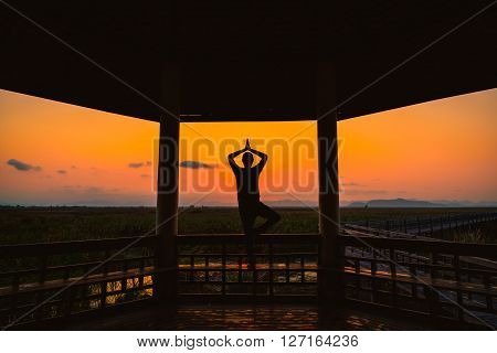 Silhouette young man playing yoga on wooden pagoda in park at sunset.