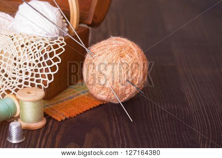 Basket with needlework and beige skein of thread with spokes for knitting on a wooden table