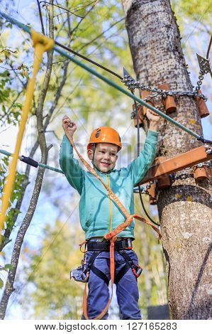 boy rejoices having overcome rope course. rope course at a summer camp. the child has successfully completed the passage of the obstacle
