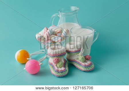 Baby Shoes And Vintage Rattle With Milk Glass