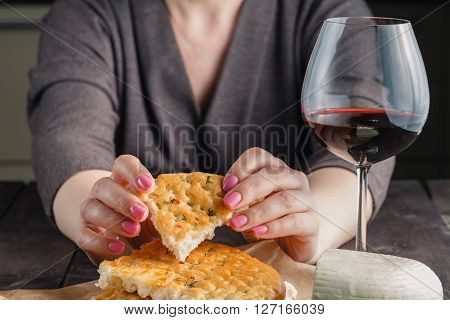 Piece of bread in woman hands with glass of wine
