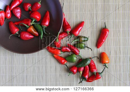Small hot red chili peppers in bowl and spilling onto a place mat