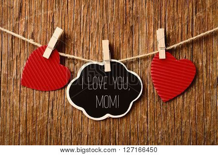 the text I love you mom written in a chalkboard in the shape of a thought bubble hanging in a rope with a wooden clothespin next to some red hearts, against a rustic wooden background