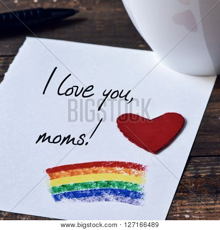 closeup of a red heart and the sentence I love you moms written in a note, which has a rainbow flag painted in it, placed on a dark wooden table next to a cup with coffee or tea