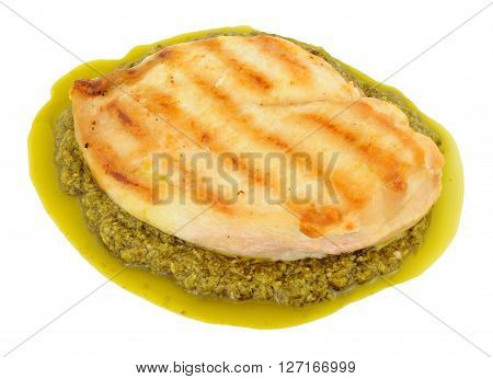 Grilled chicken breast meat on basil herb pesto isolated on a white background