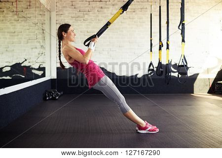 Young smiling girl in sportswear is pushing at the trx