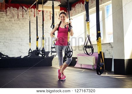 Young smiling girl in sportswear is staying and holding trx