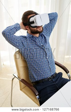 Young handsome man is smiling and watching something in virtual reality glasses