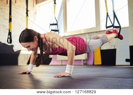Young smiling girl in sportswear is pushing while holding her feet on the trx
