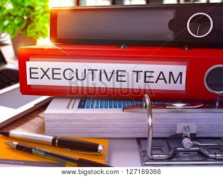 Executive Team - Red Office Folder on Background of Working Table with Stationery and Laptop. Executive Team Business Concept on Blurred Background. Executive Team Toned Image. 3D.