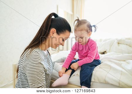 Beautiful young mother dressing her little daughter in the morning in her bedroom