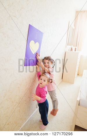 Mothers day, cute little girls holding a big greeting card for their mum