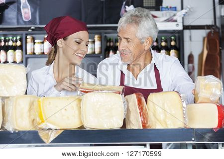 Colleagues Discussing While Holding Cheese In Store