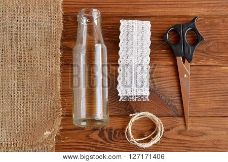 Glass bottle, scissors, burlap, cord, lace. How to make handmade vase. Top view