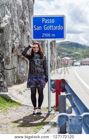 Girl under the Passo San Gottardo sign, Switzerland
